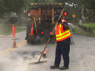 work crew filling pothole in road