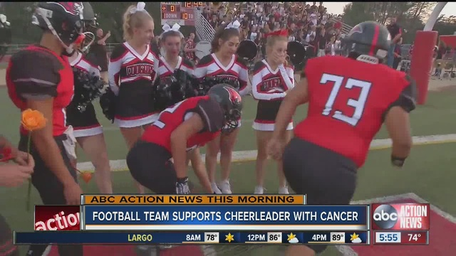 Football players place roses at feet of cheerleader recently diagnosed with leukemia