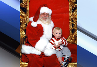 Boy signs 'help' while sitting on Santa's lap